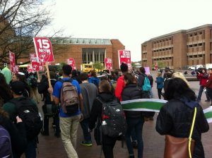 """Color photograph of a crowd of ~50 people marching, viewed from the back. Many people in the crowd hold red signs that say """"15 Now"""" and """"End poverty wages."""" Meany Hall, a large red brick building, is visible in the background."""